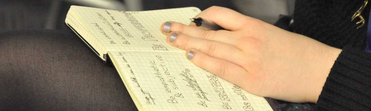 hand holding pen on notes in sketchbook